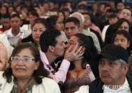 합동결혼식 중 키스하는 부부